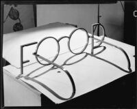 """Food"" in metal letters with the ""O-O"" forming a pair of eyeglasses, 1928-1939"