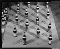 Bottles of Mission Dry Sparkling fruit beverage and drinking glasses, Los Angeles, circa 1930