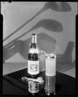 "Bottle of ""Mission Dry Sparkling"" beverage on a table beside 2 full glasses, Los Angeles, circa 1930"