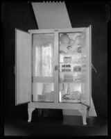 Open icebox with a block of ice and food inside, 1930-1937