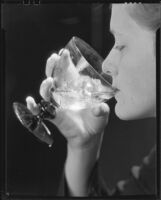 Woman drinking a glass of ice water, 1930-1937