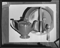 Silver or pewter coffee pot, plate and silverware at the Brock & Company jewelry and gift store, Los Angeles, 1928-1938