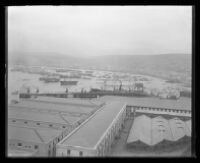Overhead view of a foggy shipping yard and adjacent docks.