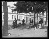 City goers relax in a shaded area of a cobbled stone street.