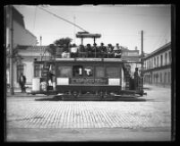 Residents ride a trolley through a city street.