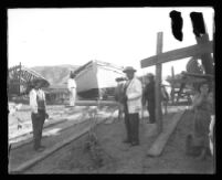 Men and women look directly into the camera during ship construction on a beach.