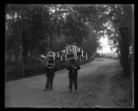 Two men stand in the middle of a country road both carrying a large stack of chairs.
