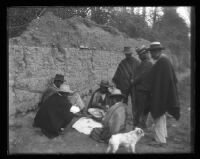 Seven men and dog rest on the side of the road.
